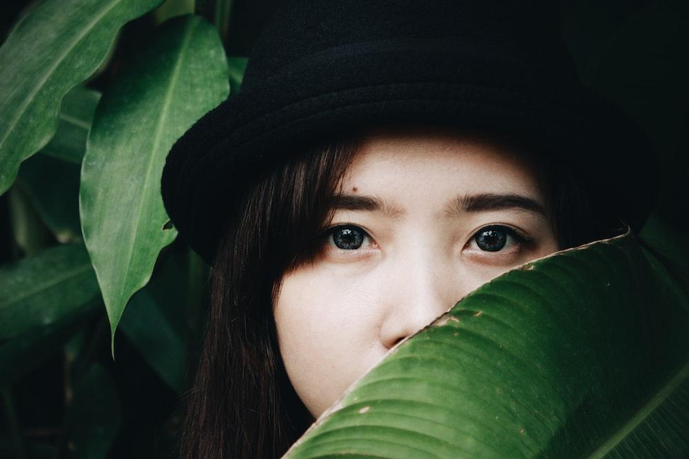 woman hides behind broad green leaf