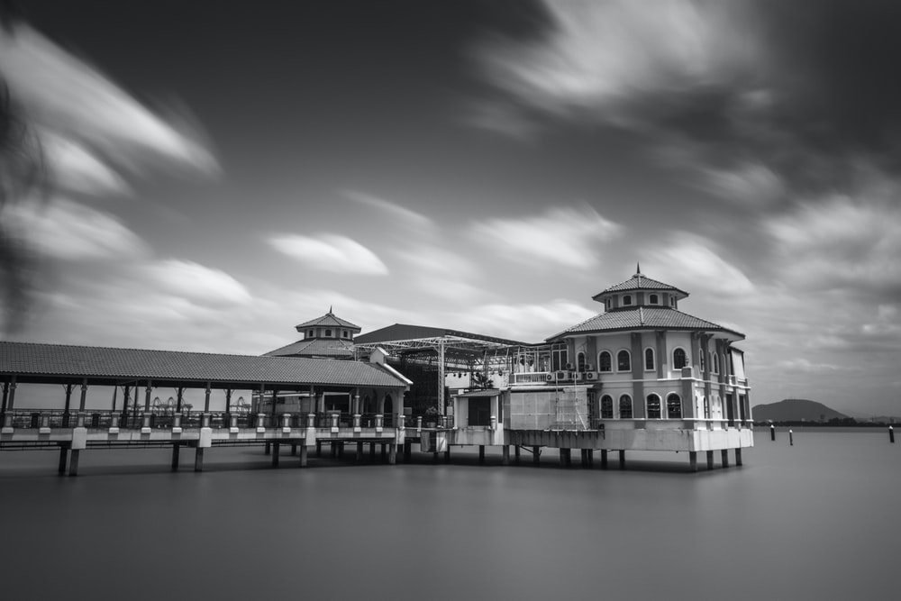 black and white picture of a building on water