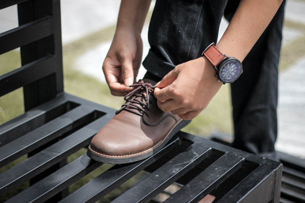 man tying a shoe lace