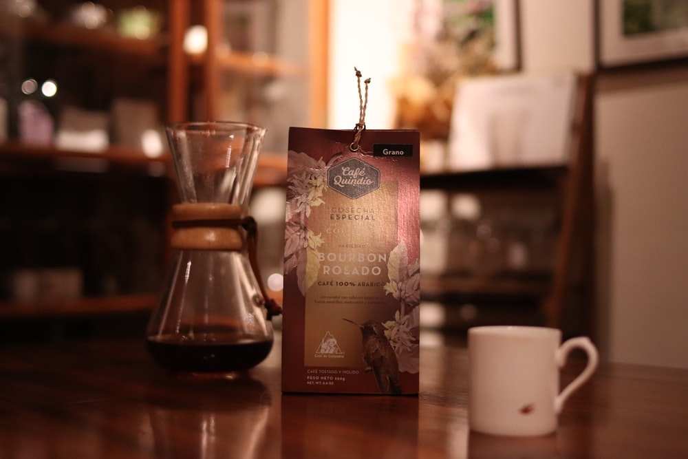 coffee in coffee press, box, and white ceramic mug on table