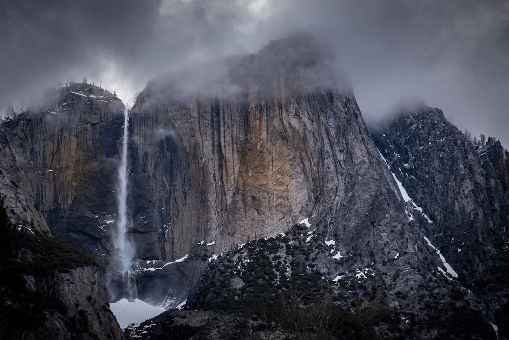 mountain cliff under nimbus clouds