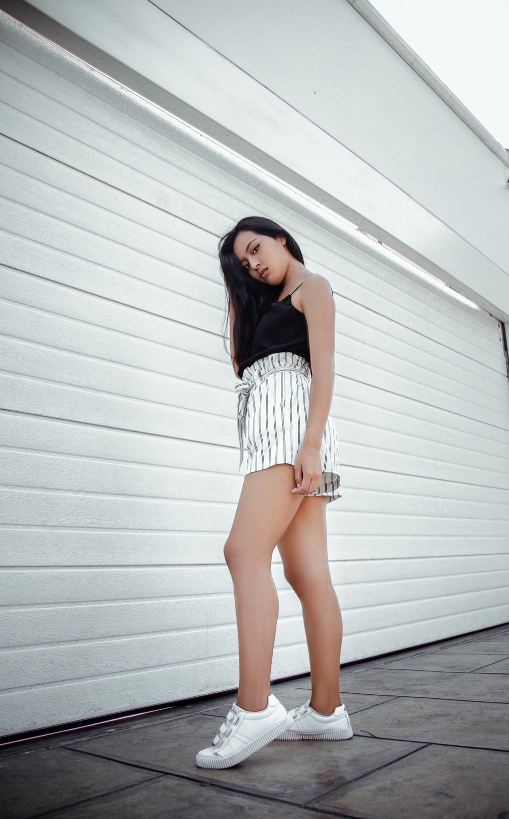 woman in a black tank top and white striped shorts