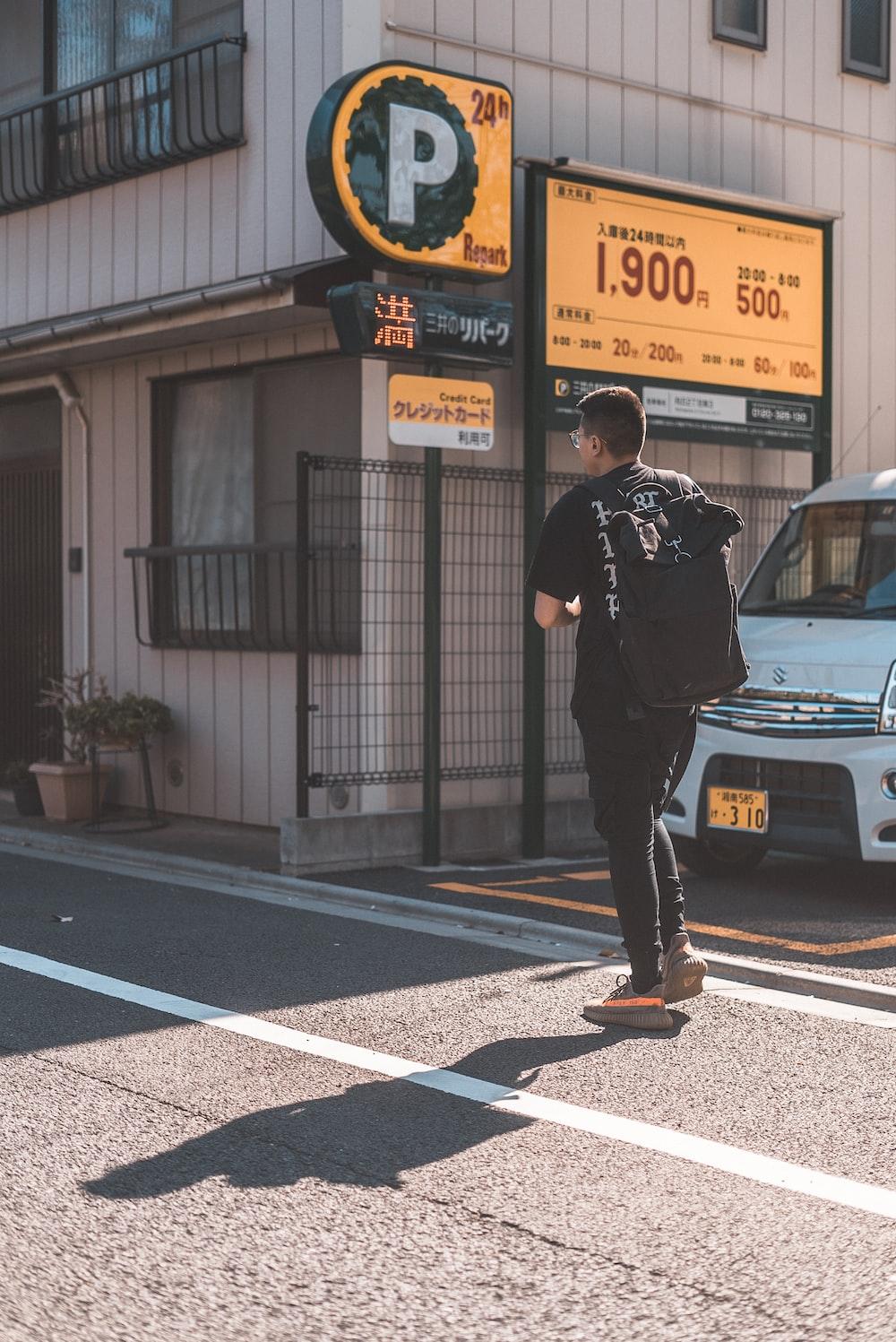 man in black tee shirt crossing road