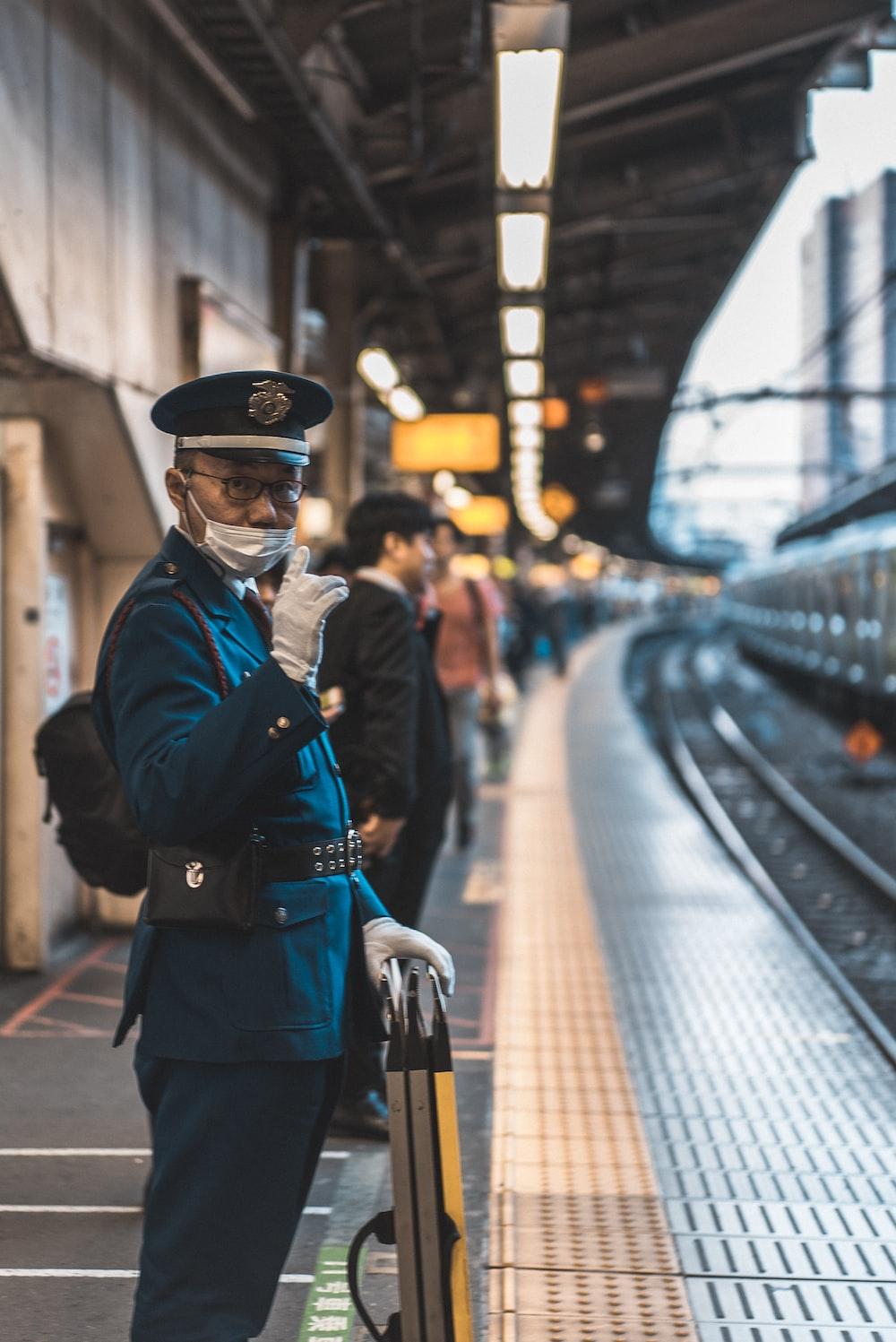 man in a uniform by train tracks