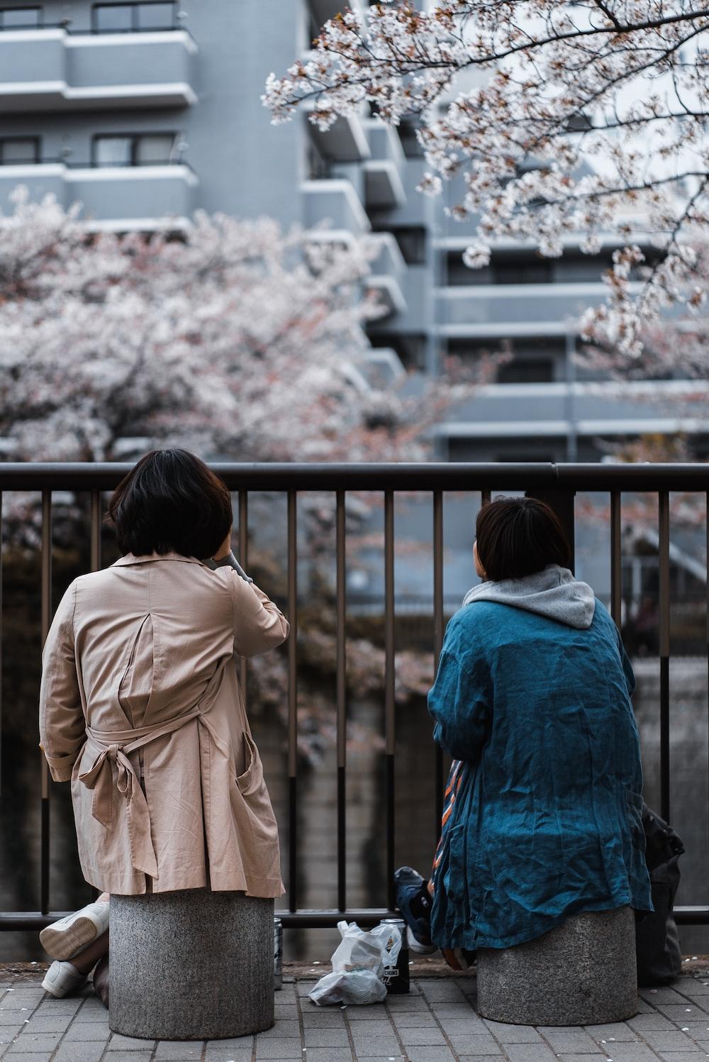 two woman sitting beside railing near building