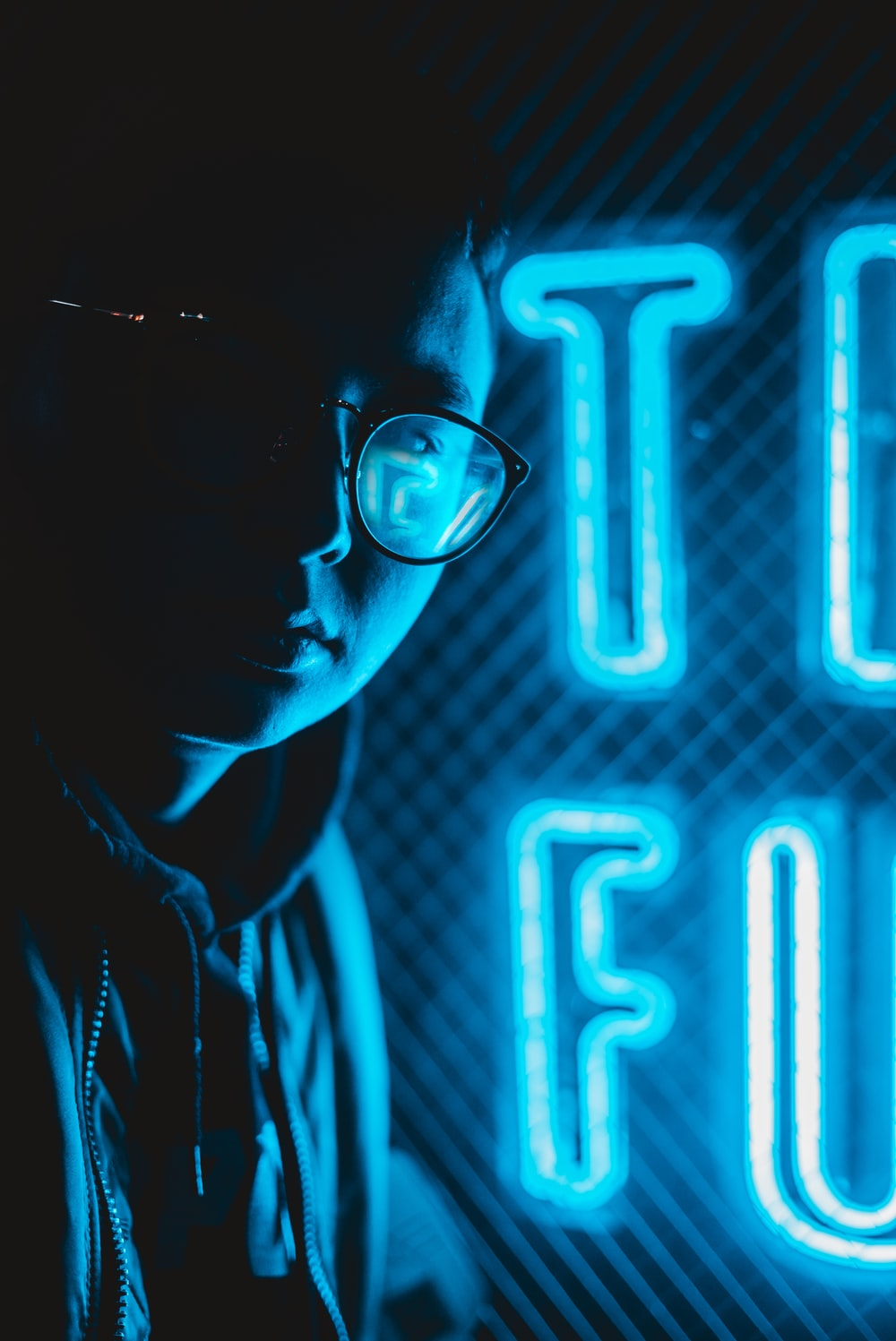 person in eyeglasses beside blue neon signage