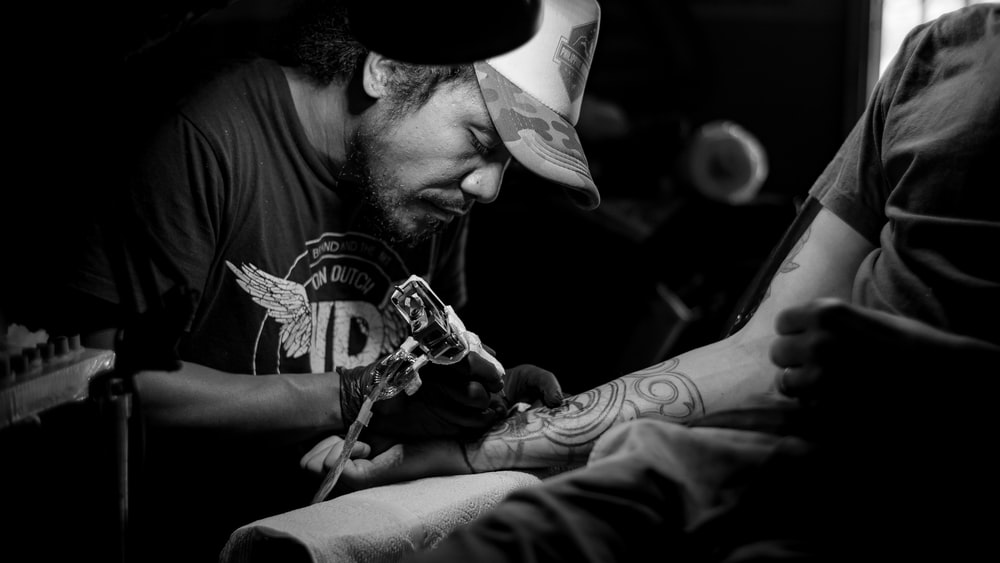 grayscale photo of man doing tattoo