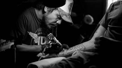 grayscale photo of man doing tattoo tattoo zoom background