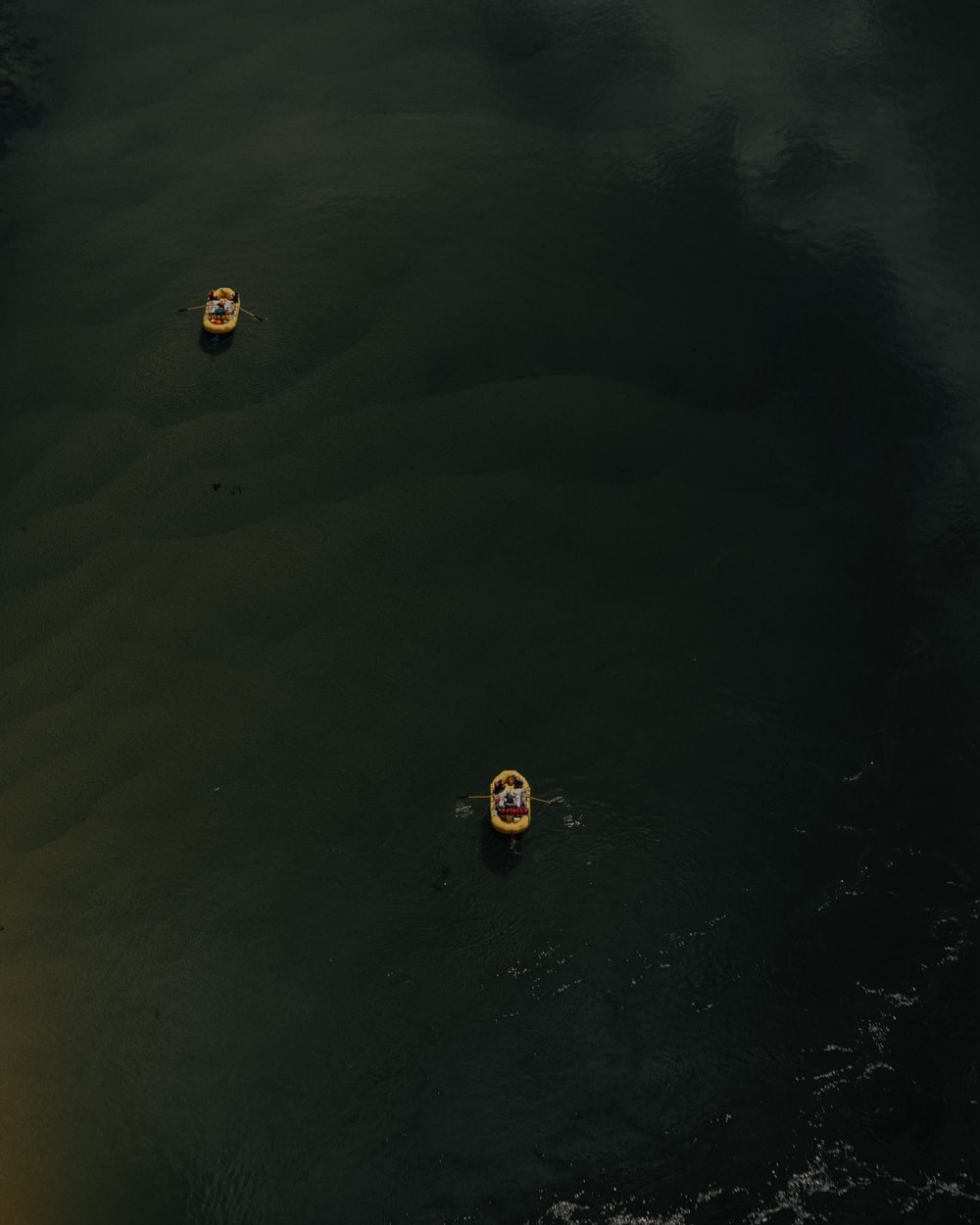 two yellow boats on body of water