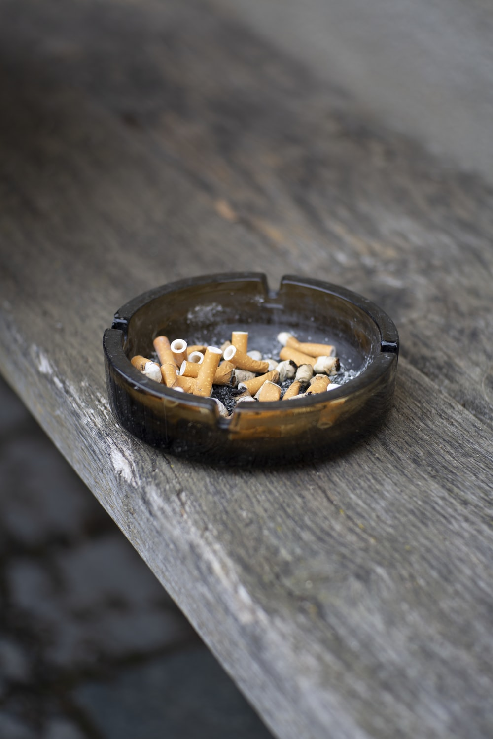 round gray ashtray on brown wooden table top