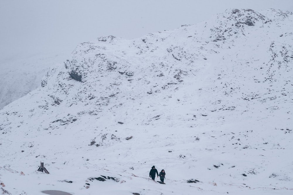 two people walking on snow