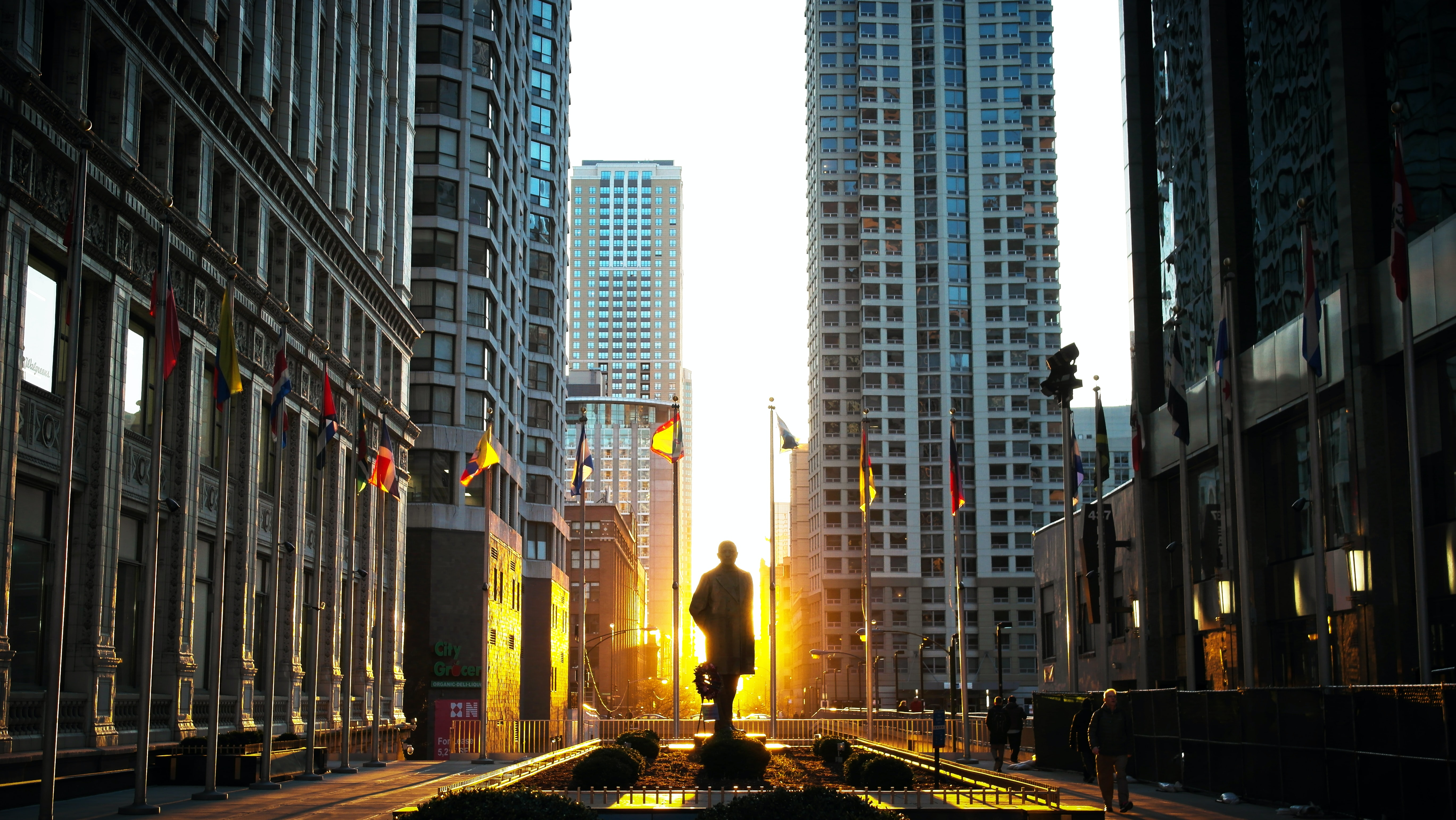 silhouette of statue at the park surrounded by high rise building