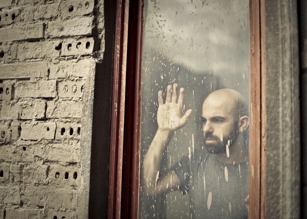 man leaning on window