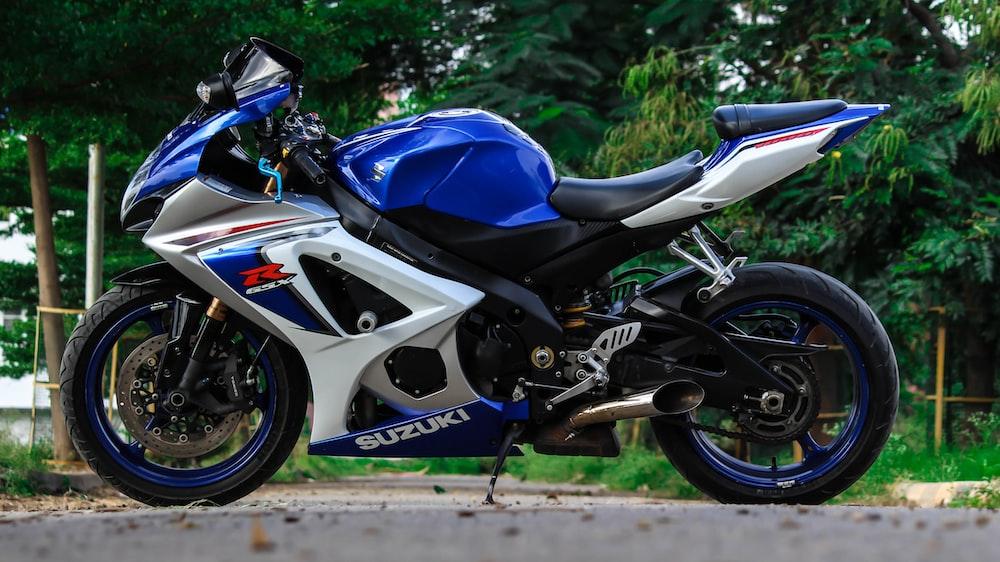 blue and white Suzuki sports bike parked during daytime