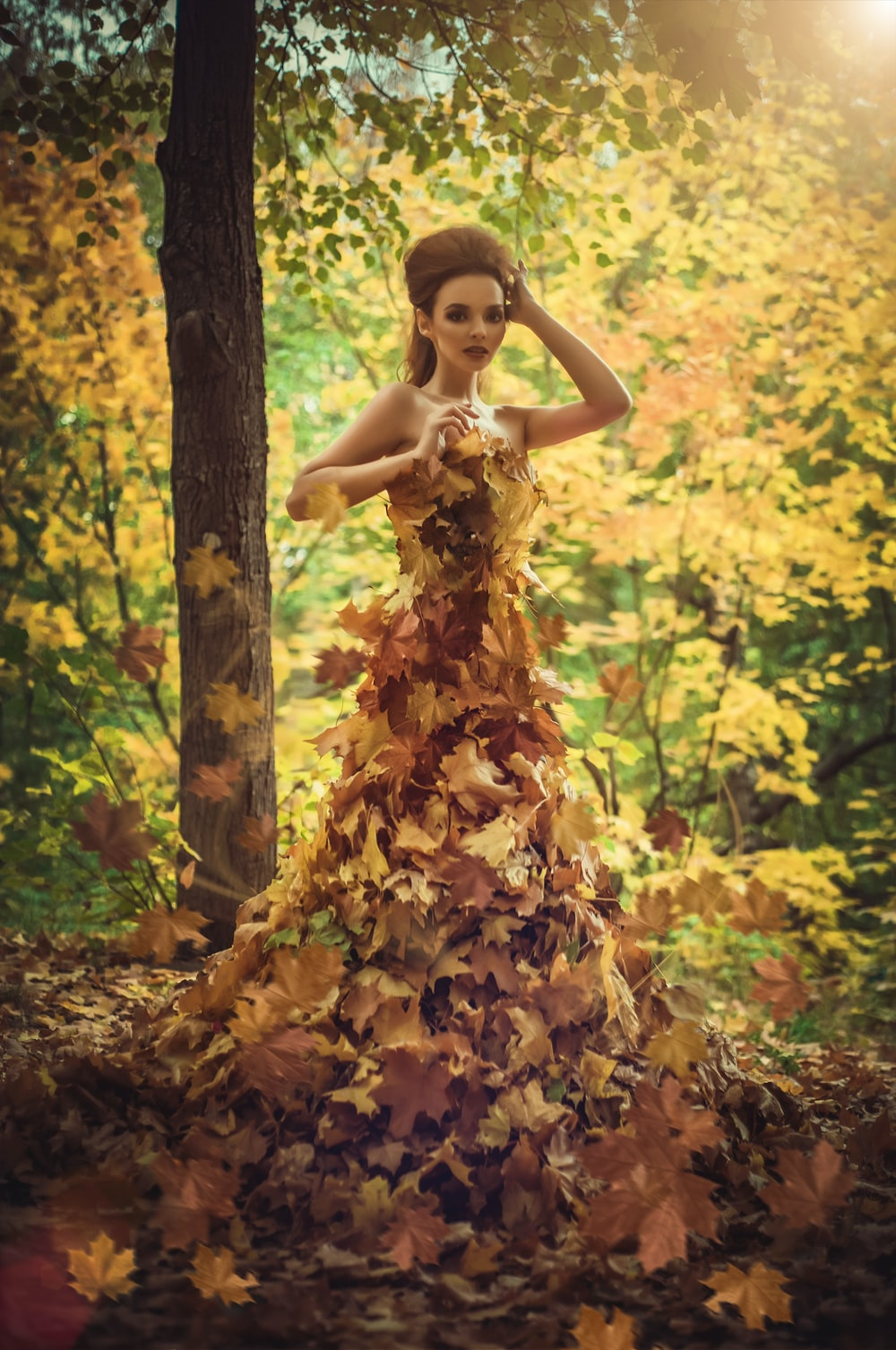 woman standing surrounded by leaves