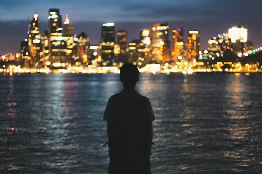 silhouette of person standing near light buildings