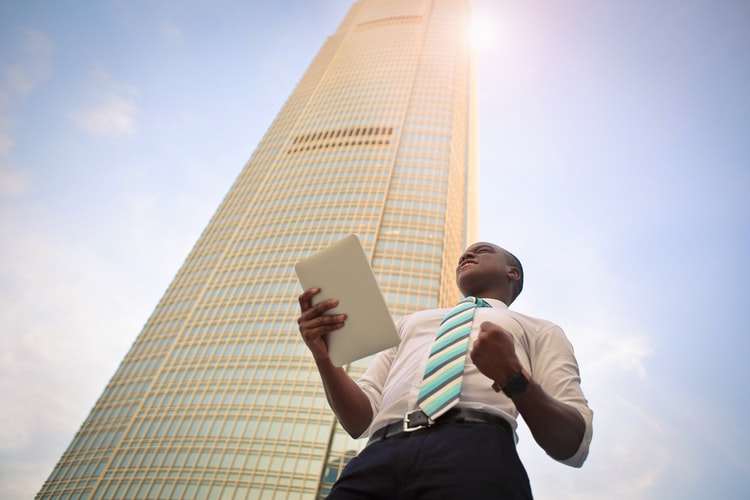 Man wearing tie standing in front of a high-rise building