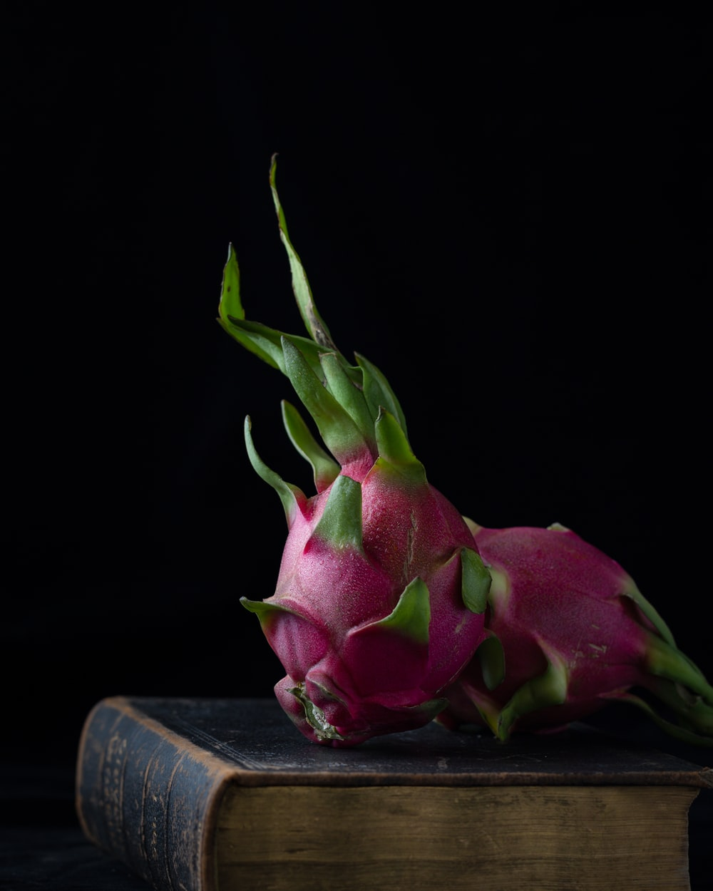 two pink-and-green dragon fruits on hardbound book