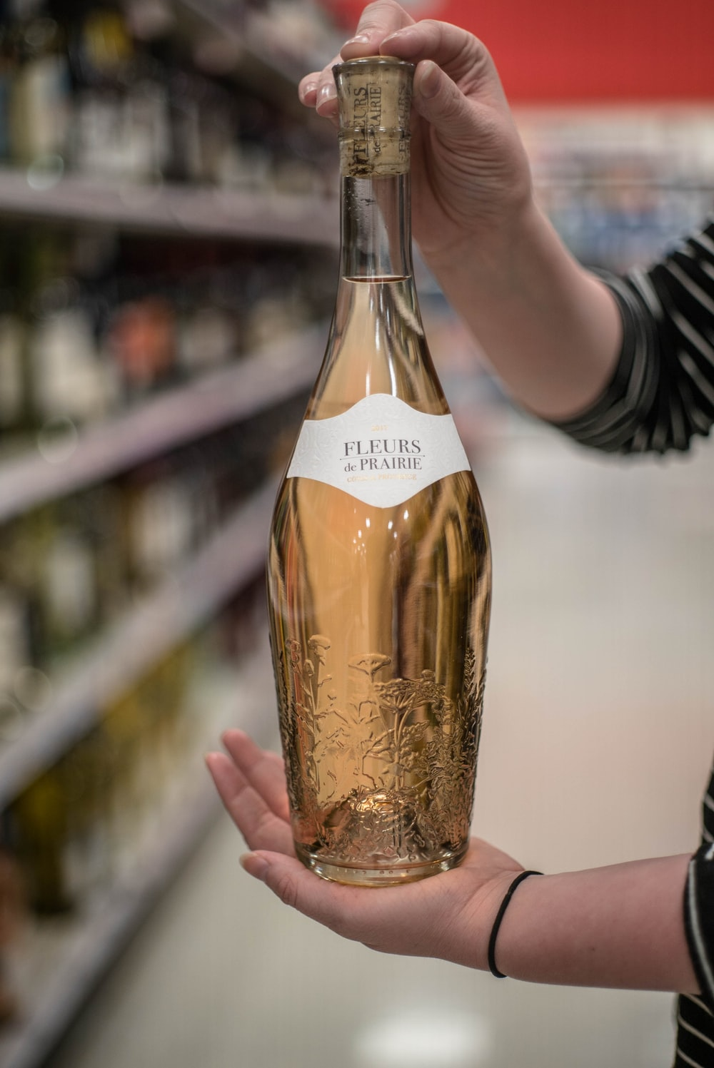 person holding Fleurs bottle inside store