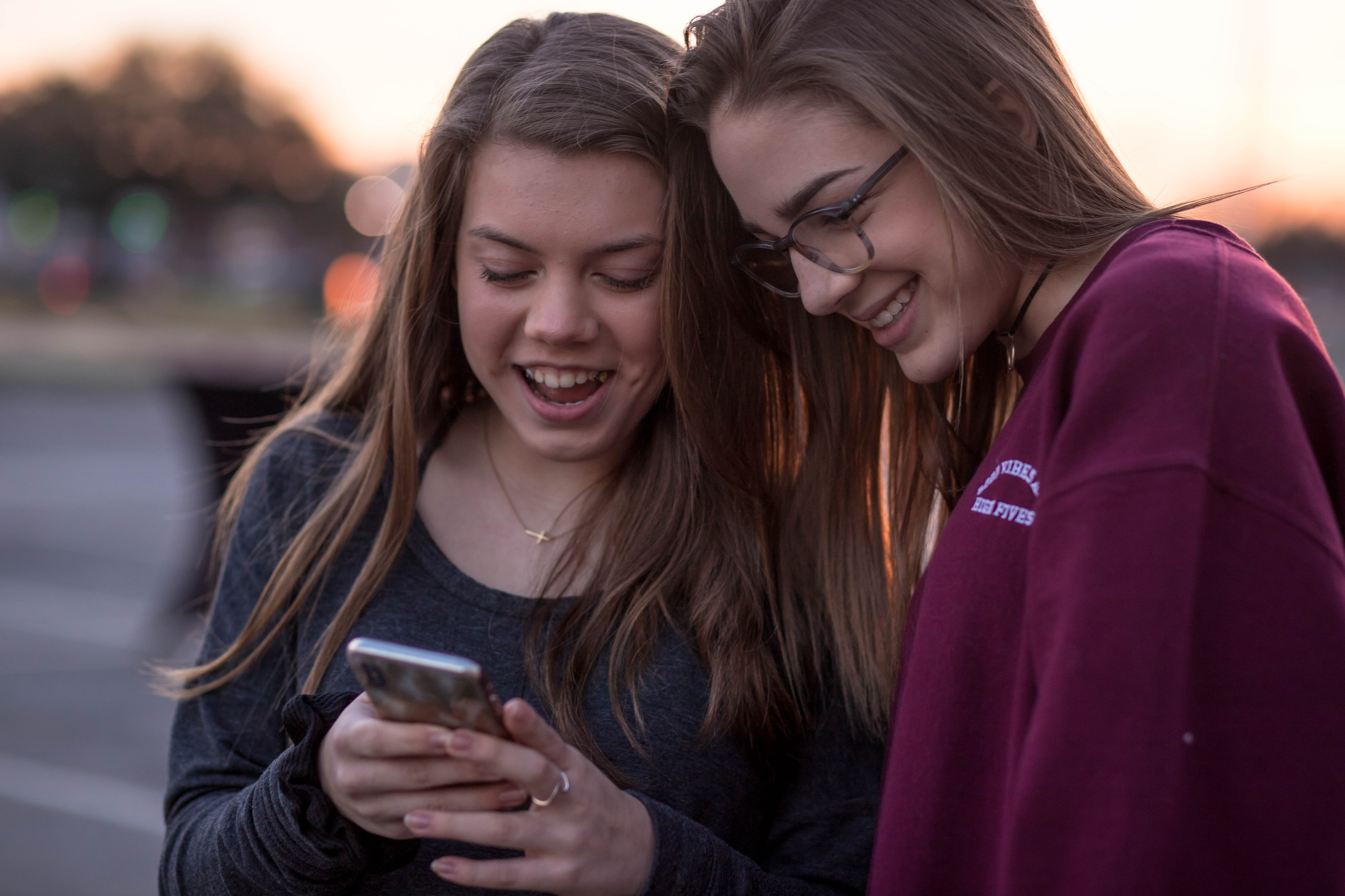 selective focus photo of two women looking on black smartphone
