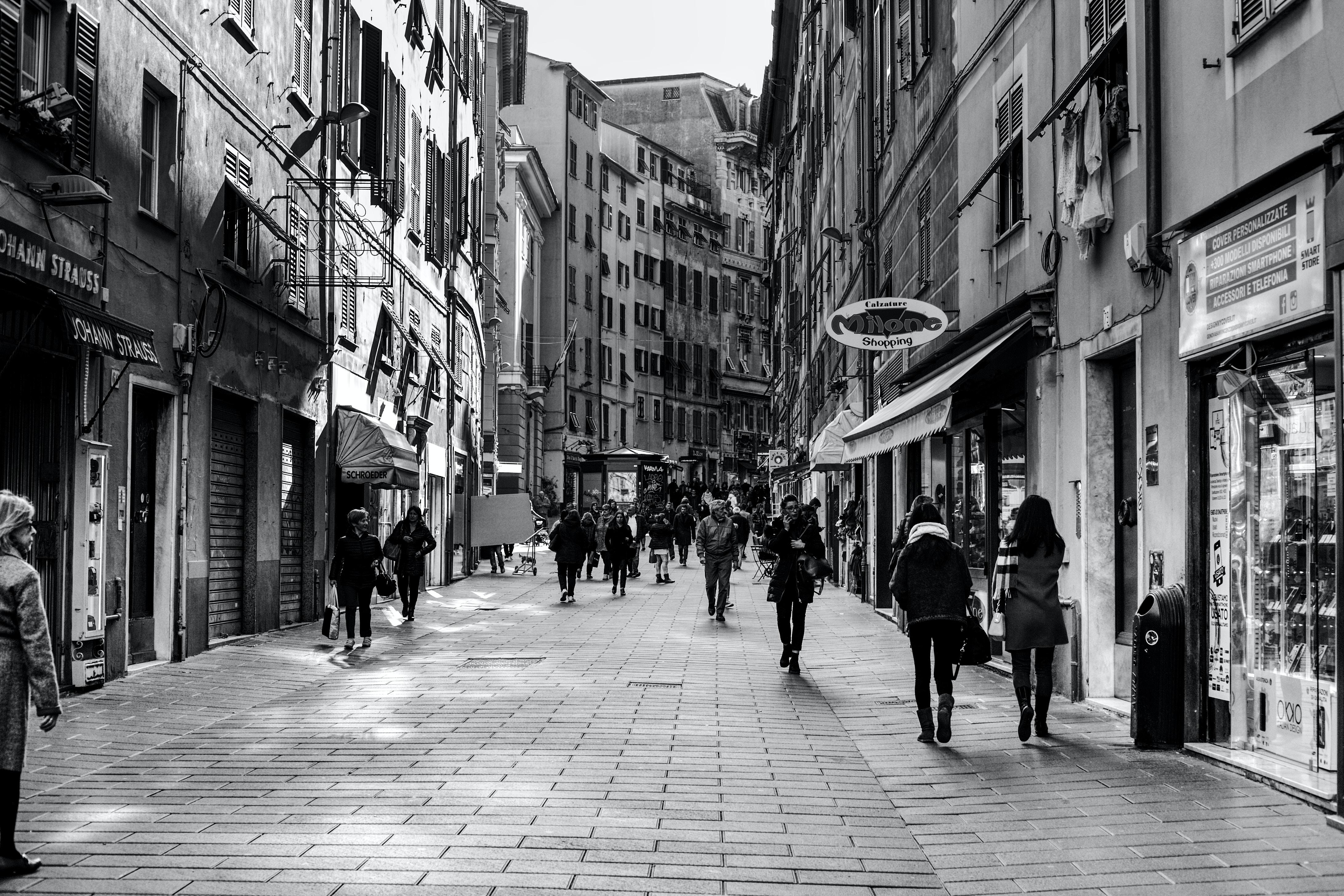 grayscale photo of people walking between buildings during daytime