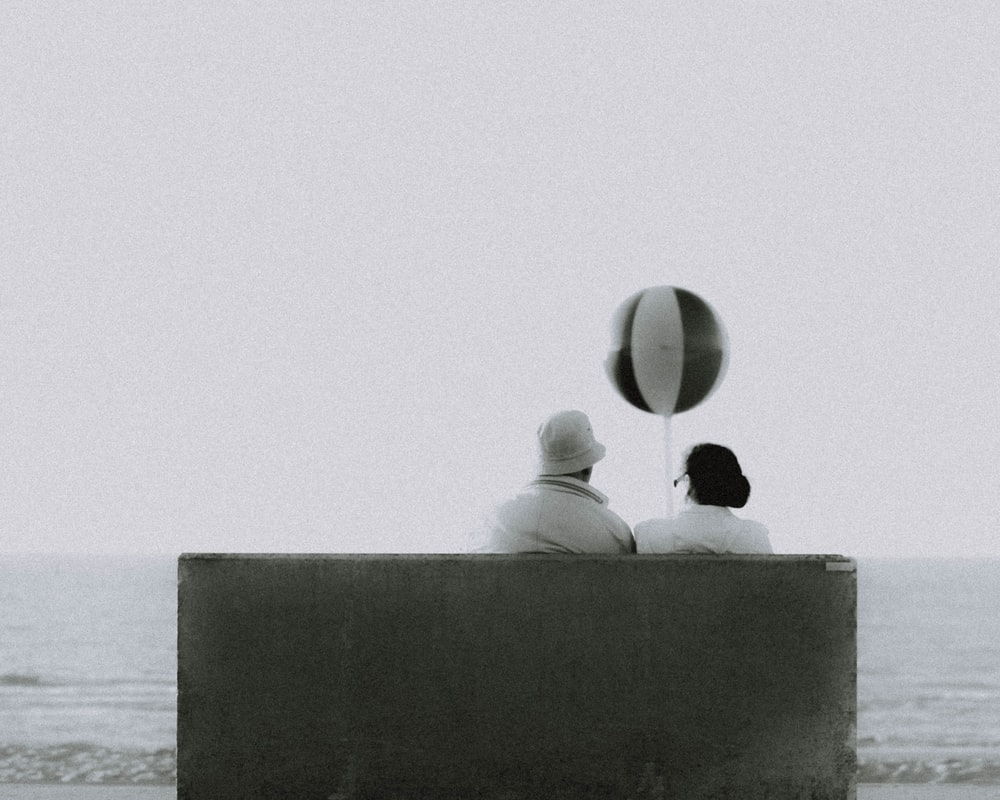 couple sitting on bench in front of beach