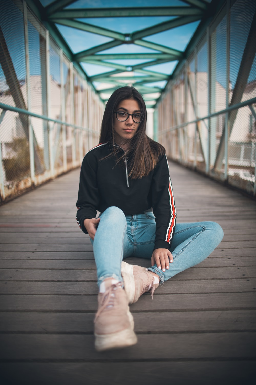 woman wearing jacket and denim jeans sitting on brown bridge