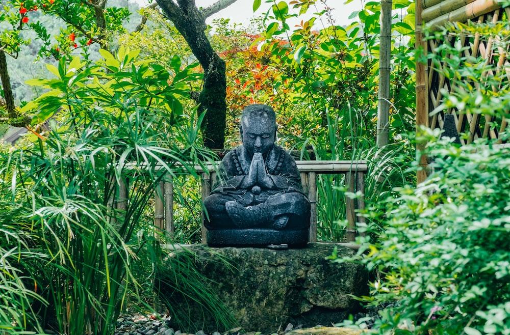 Buddha statue on green rock