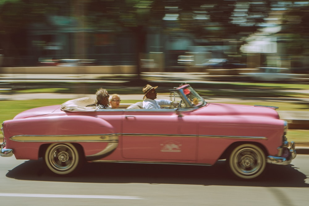three person riding convertible coupe passing by on road in time lapse photography