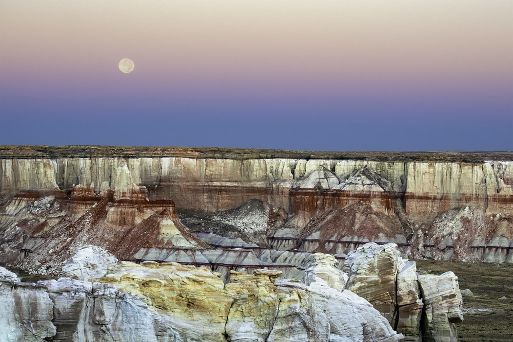 canyon under clear sky with visible moon at daytime