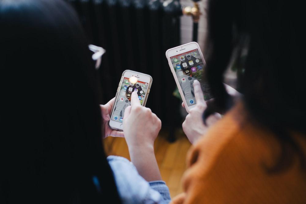 two women operating smartphone