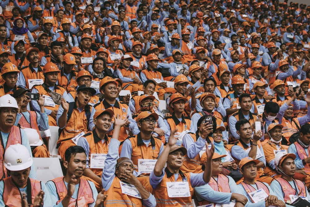 group of people wearing orange caps