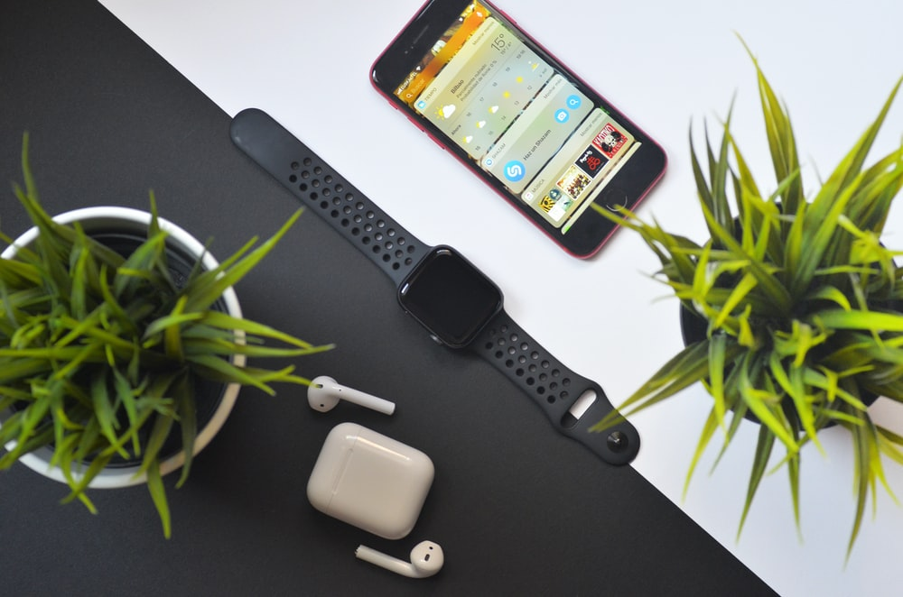 Apple Watch between iPhone and AirPods on table