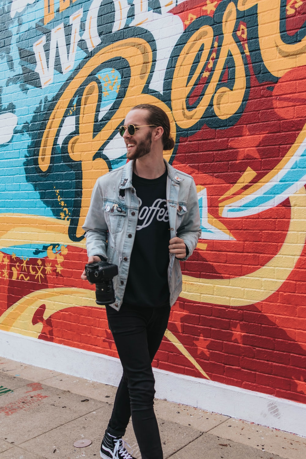 man holding DSLR camera standing on front of wall with graffiti