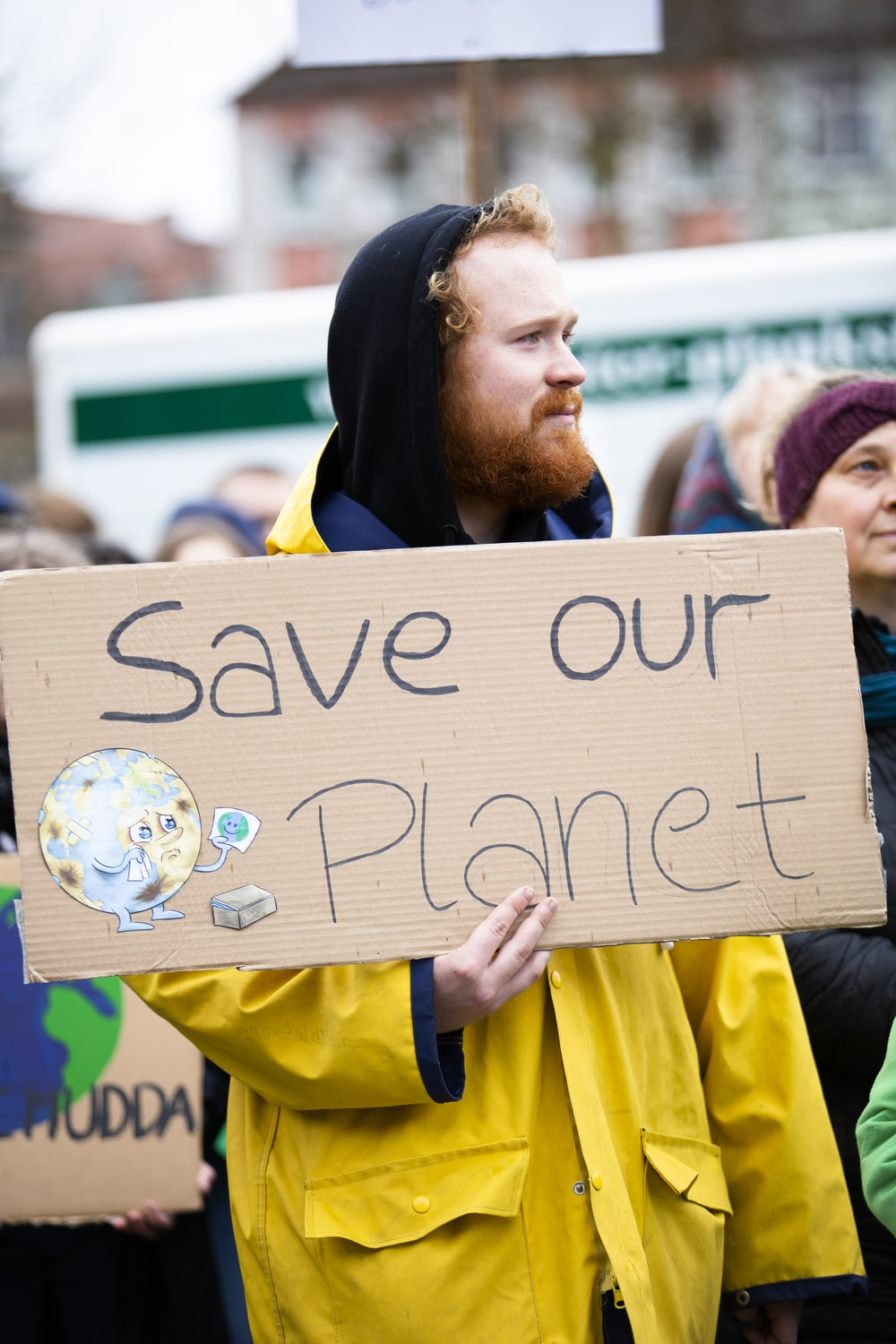 person holding brown save our planet cardboard poster
