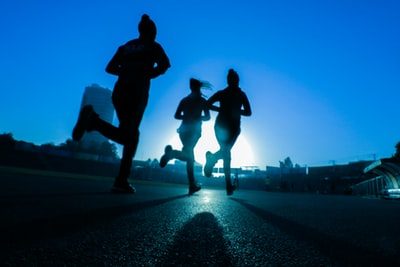 silhouette of three women running on grey concrete road sports zoom background