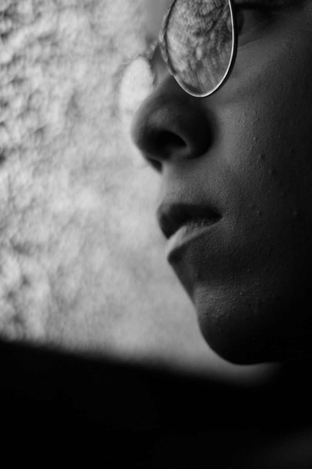 grayscale photo of person wearing eyeglasses looking at glass