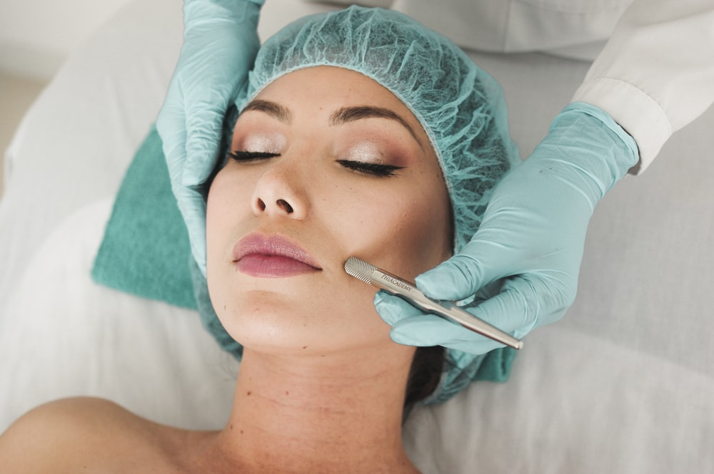 woman doing liposuction on her face