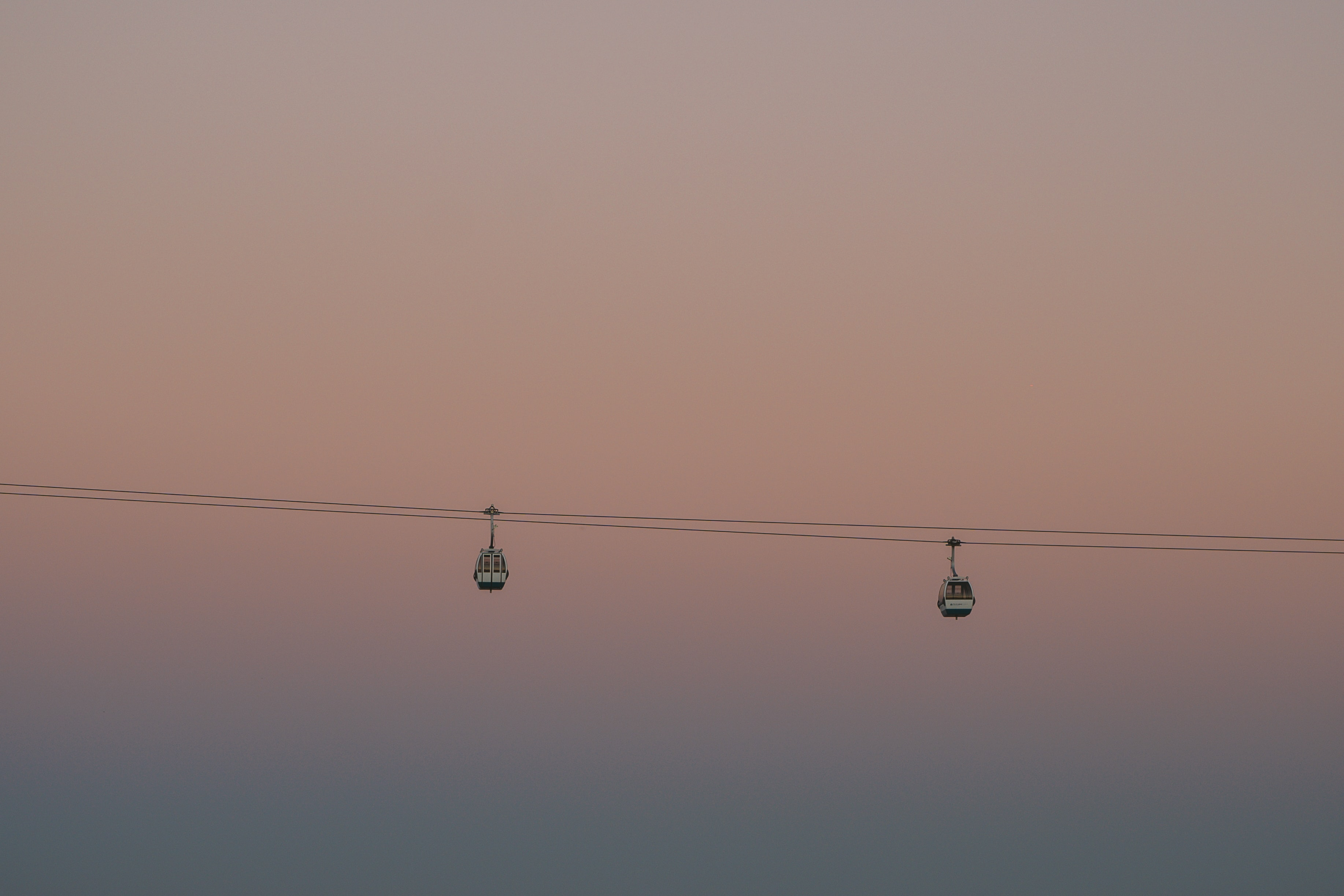 two cable cars traveling during sunset