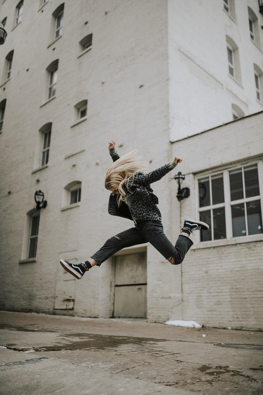 woman jumper near white concrete building