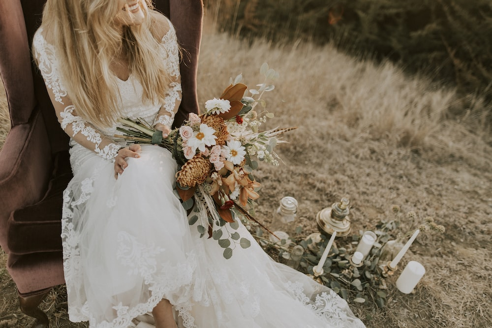 woman in white bridal gown sitting on brown wing chair while holding bouquet