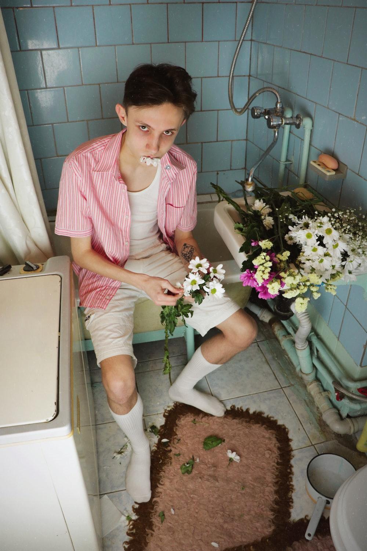 man sitting on bath tub holding white flower