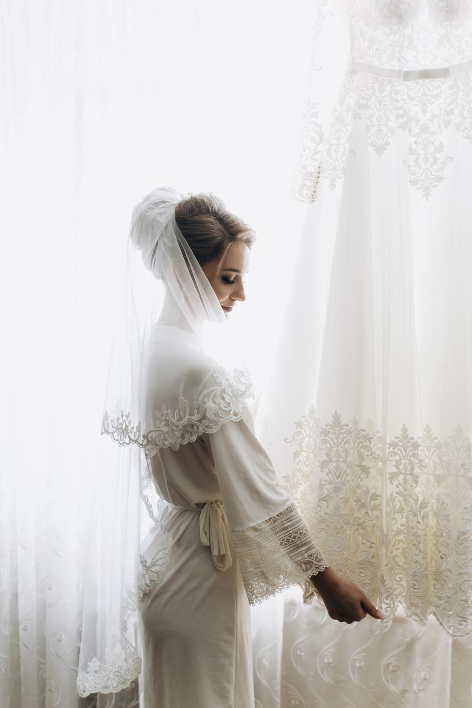 woman standing beside curtain