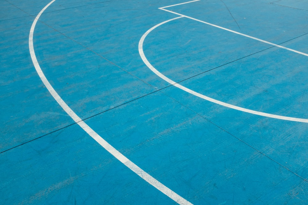 white painted lines on blue court floor