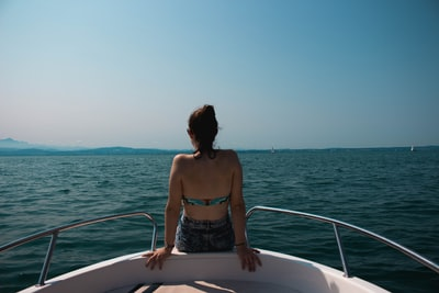 woman sitting on edge of boat back zoom background