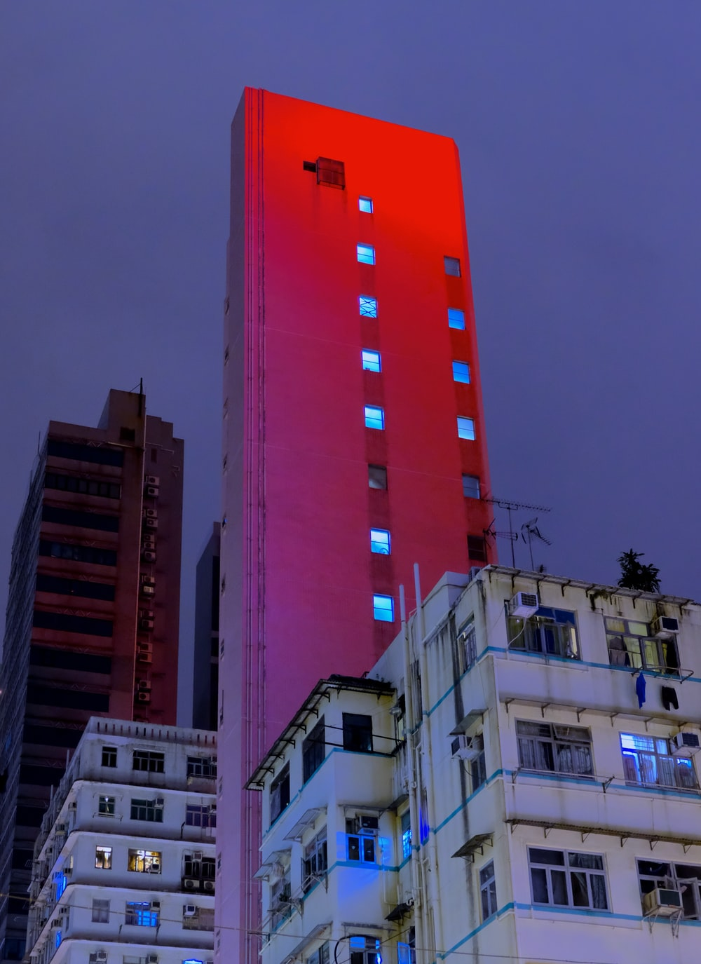 shallow focus photography of red high-rise building at night time