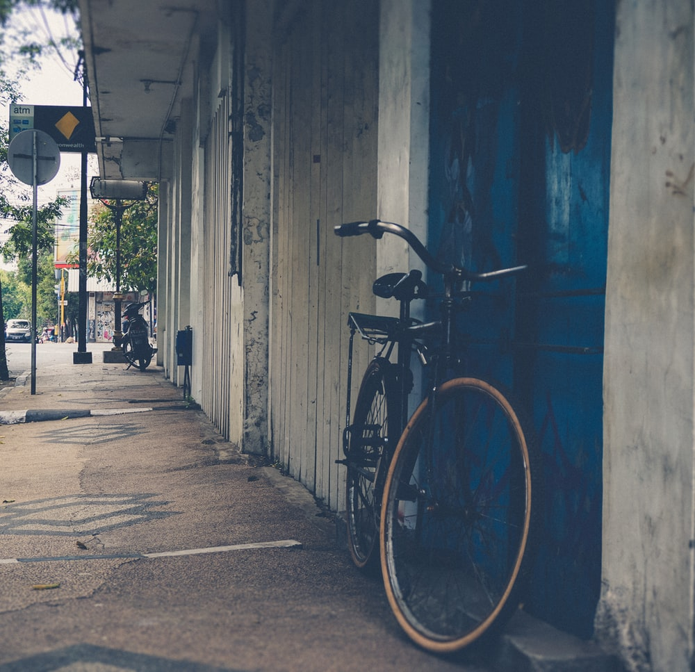 black commuter bike park near blue door