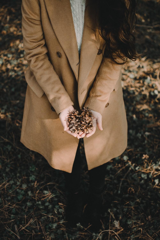 woman wearing brown blazer holding dried leaf