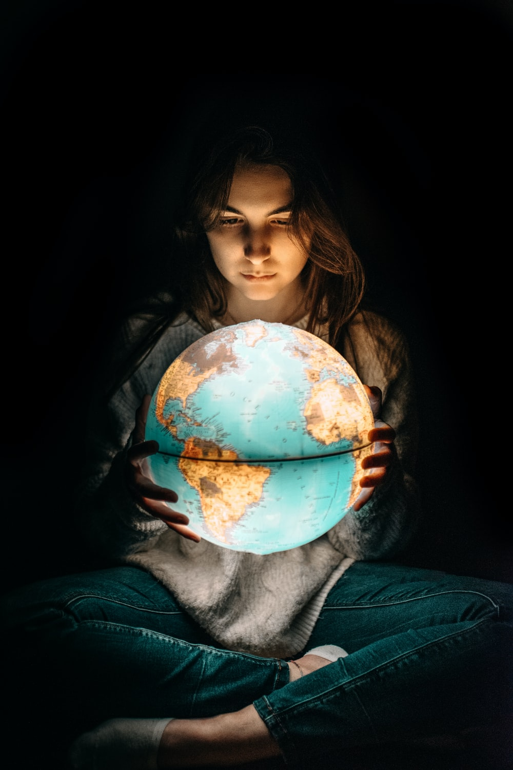 woman holding glowing earth globe