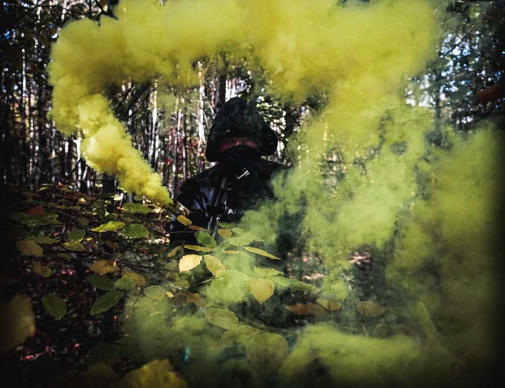 person surrounded by yellow smoke on forest
